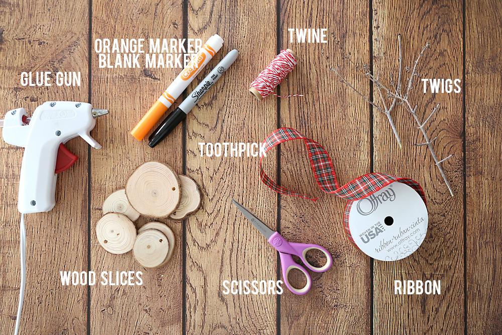 Snowman ornament supplies: orange and black markers, twine, sticks, toothpick, ribbon, wood slices, scissors, glue gun