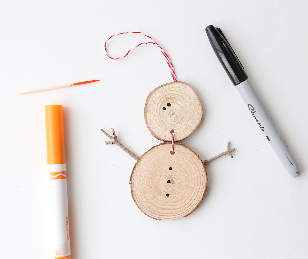 Wood slice snowman with dots for eyes and toothpick end colored orange