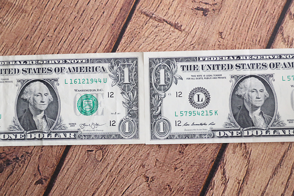 A close up of two one dollar bills taped together