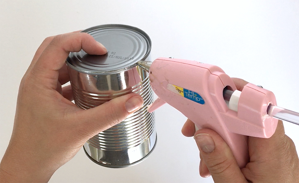 Hands gluing the bottom of the can back on with hot glue