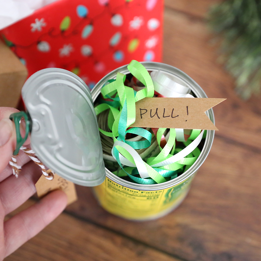 Pop top can of peaches with the top open to show ribbons and a tag that says pull