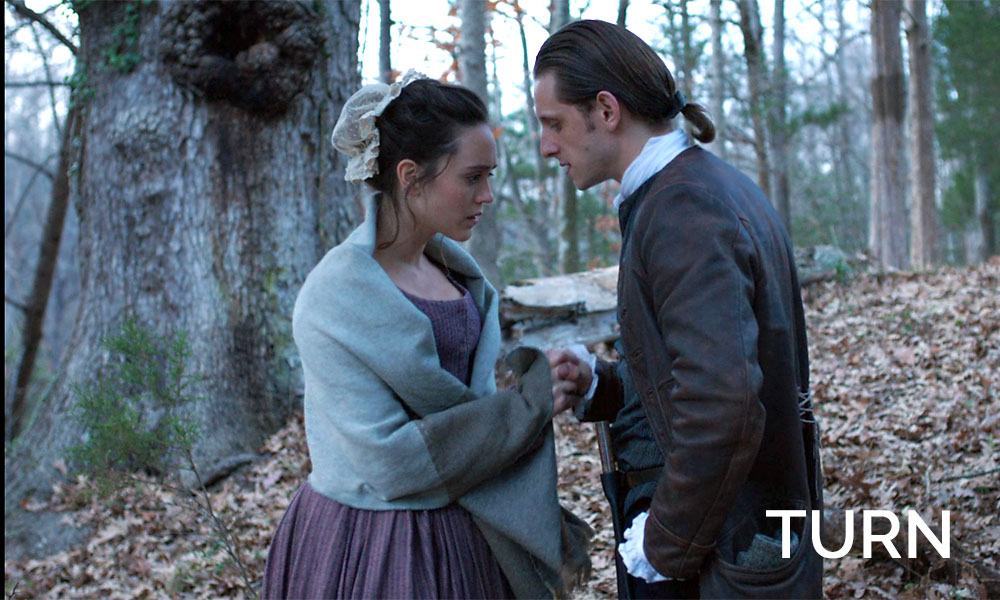 A man standing next to a woman in Revolutionary War times in the show Turn