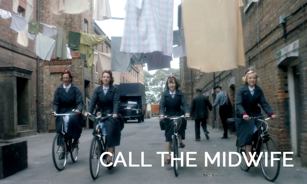 A person riding a bicycle on a city street in Call the Midwife