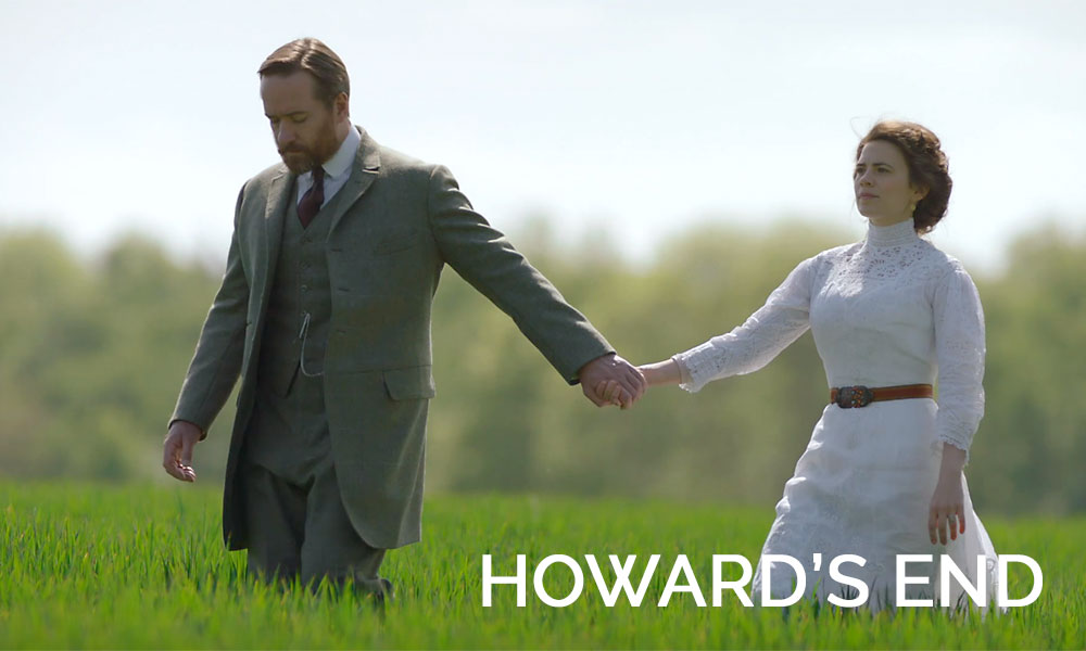 A man wearing a suit holding hands with a woman in a dress in the movie Howard\'s End