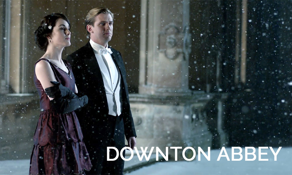 A woman standing in front of a building, with Downton Abbey