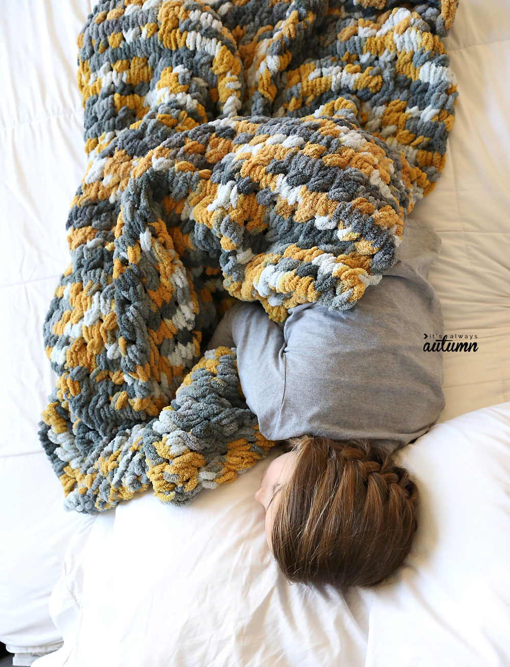 Girl curled up on a bed with a finger knit blanket