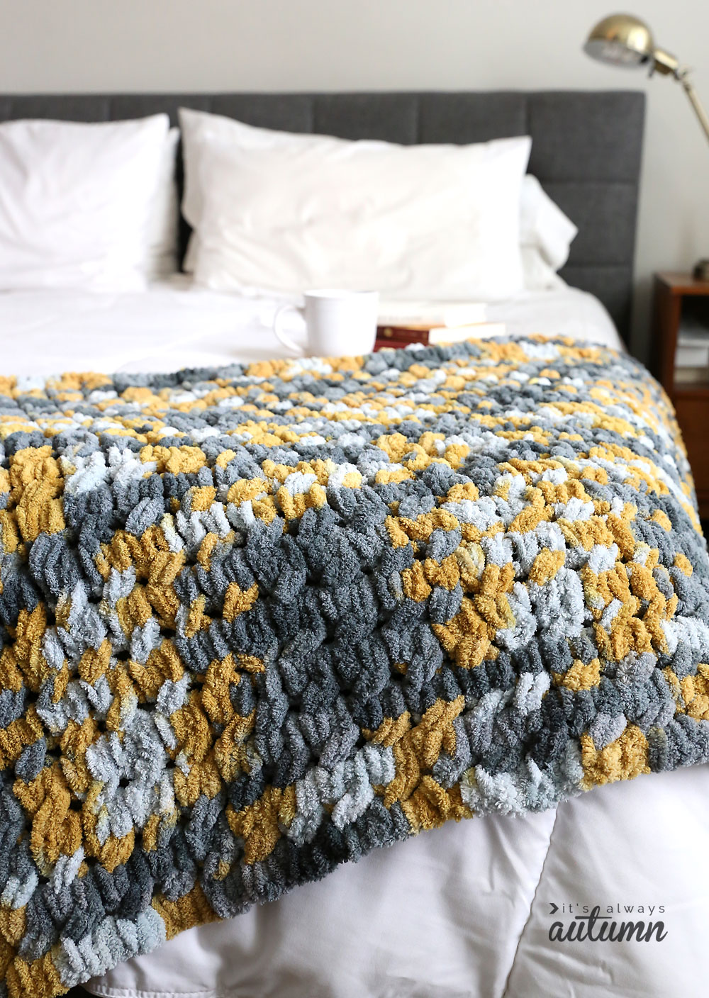 Grey and yellow cable knit blanket on a bed