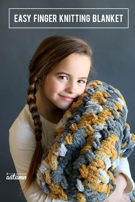 Girl holding a grey and yellow loop yarn blanket
