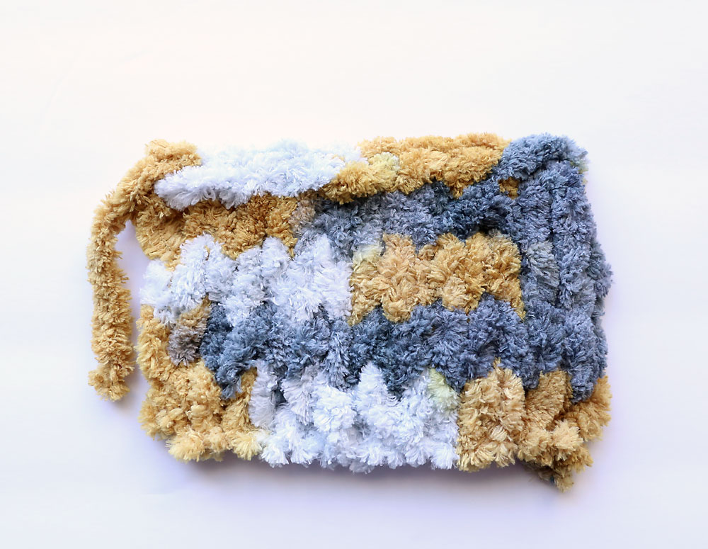 It's super easy to make this pretty cable knit blanket using loop yarn! You can finger knit without needles or any knitting experience.