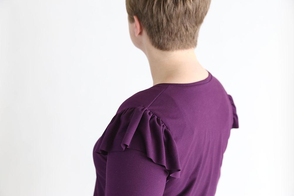 A closeup of shoulder ruffles on a purple t-shirt