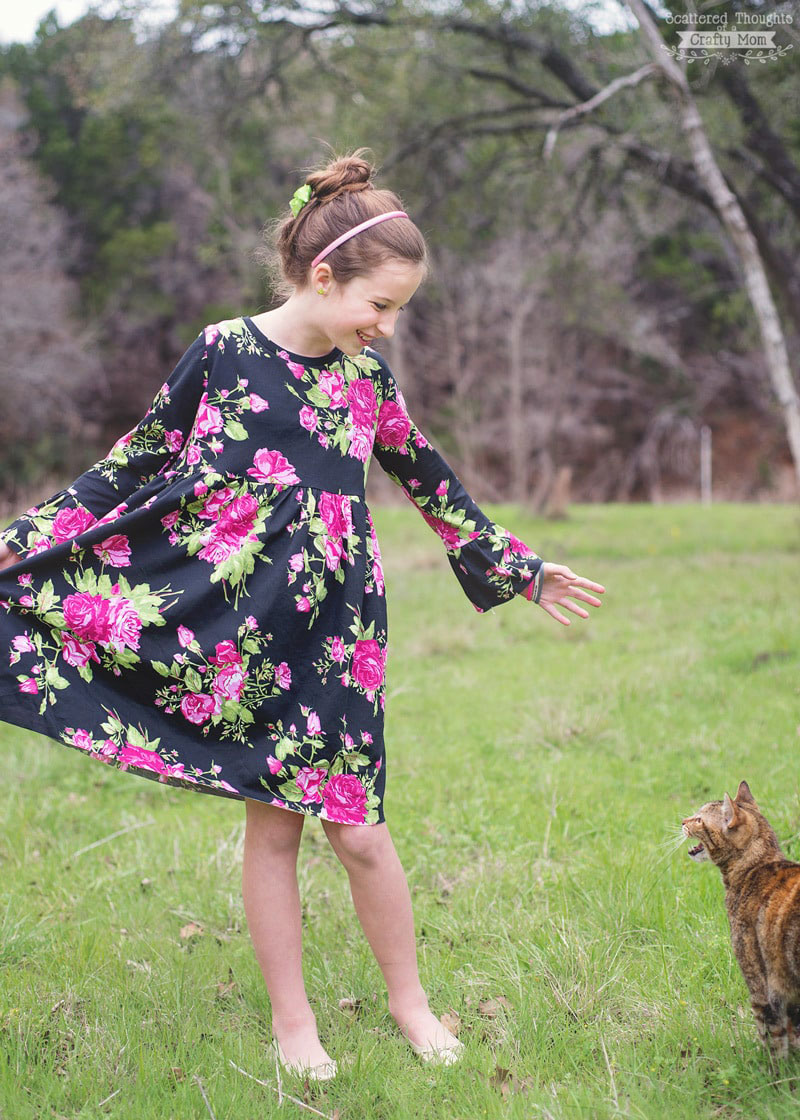 A little girl that is standing in the grass wearing a long sleeve dress