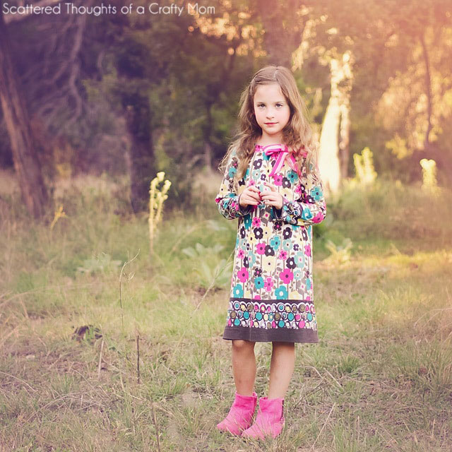 A little girl standing in a field wearing a long sleeve dress