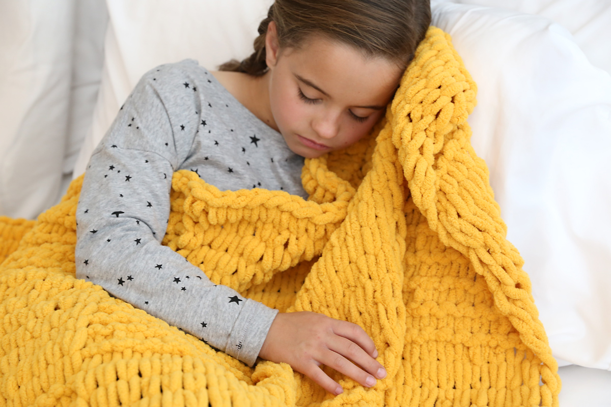 Girl sleeping with yellow loop yarn blanket