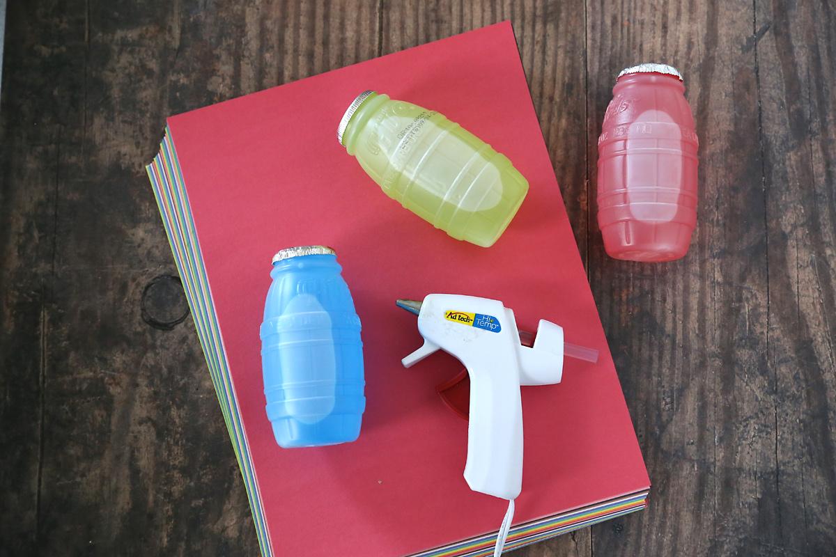 Christmas juice treat supplies: juice, construction paper, hot glue gun