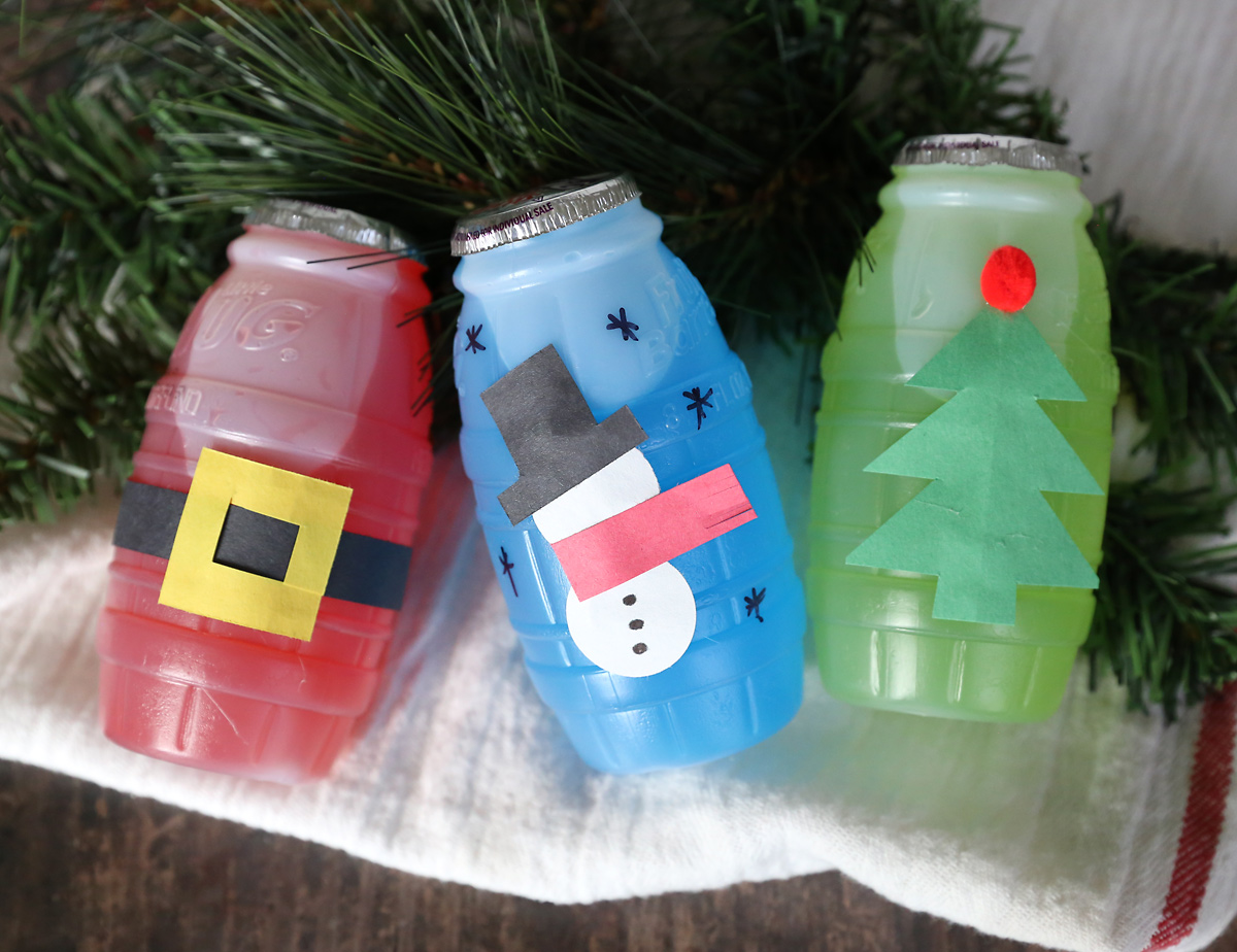 Juice treat jugs decorated for Christmas: Santa\'s belt on the red jug, paper snowman on the blue jug, Christmas tree on the green jug