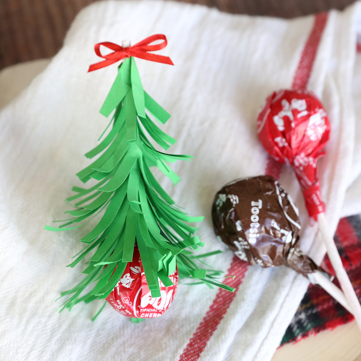 Tootsie pop sucker sitting upside down, with stick covered with strips of green paper to resemble Christmas tree