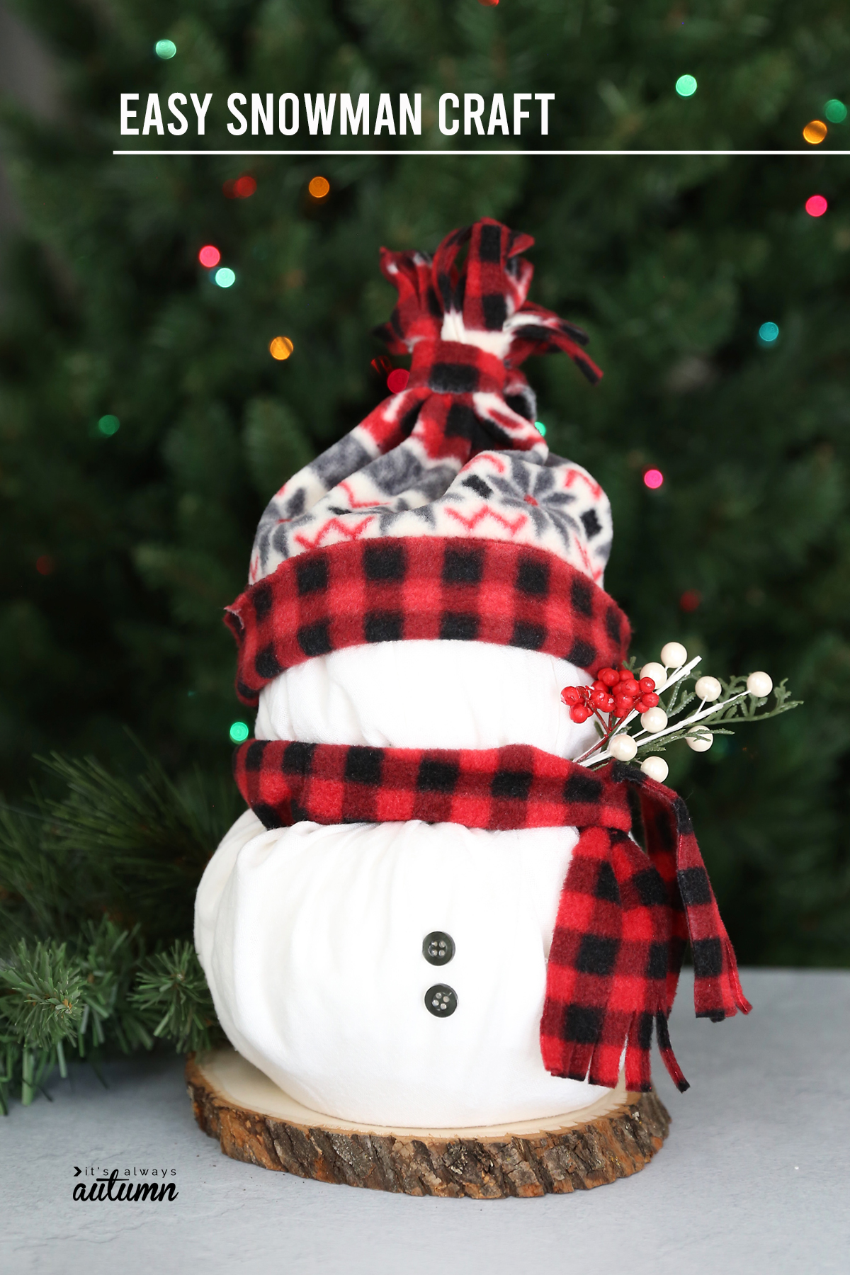 Snowman craft made from two rolls of toilet paper wrapped in white fabric with fleece scarf and hat