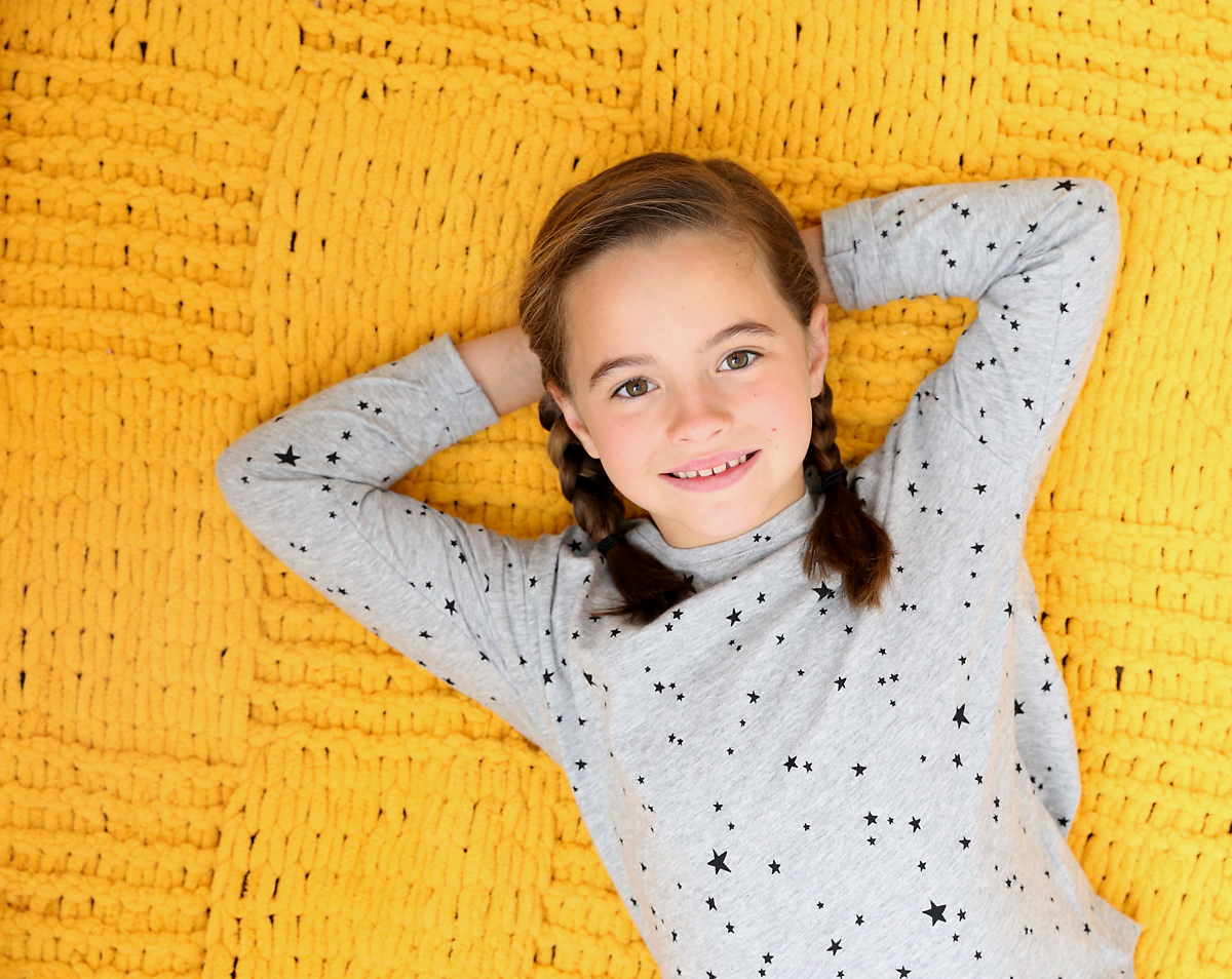 Girl laying on a yellow blanket made from loop yarn