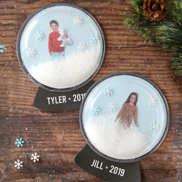 Snow globe craft made with clear plastic plates with pictures of children inside