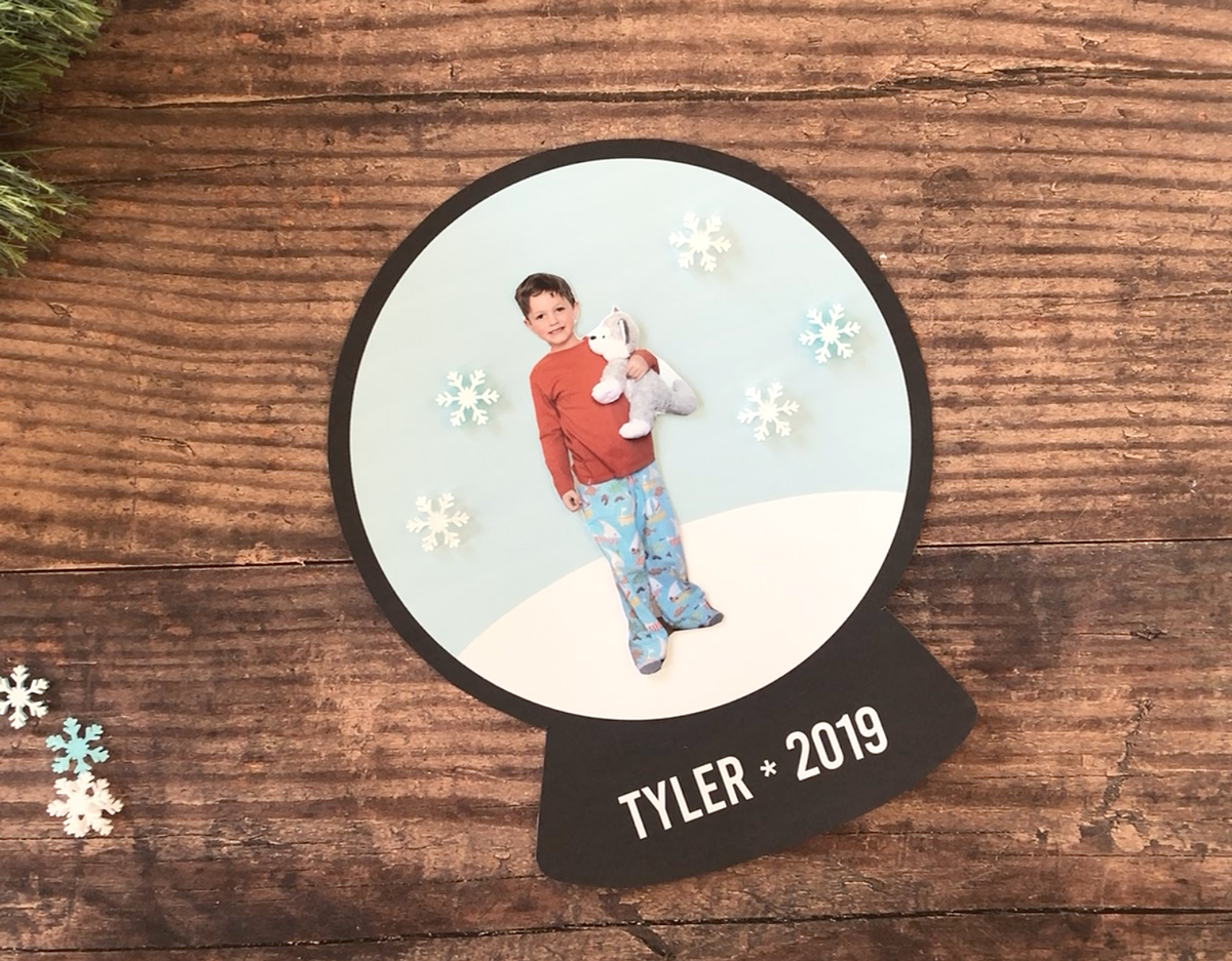 Photo of child cut out and glued onto printed snowglobe template