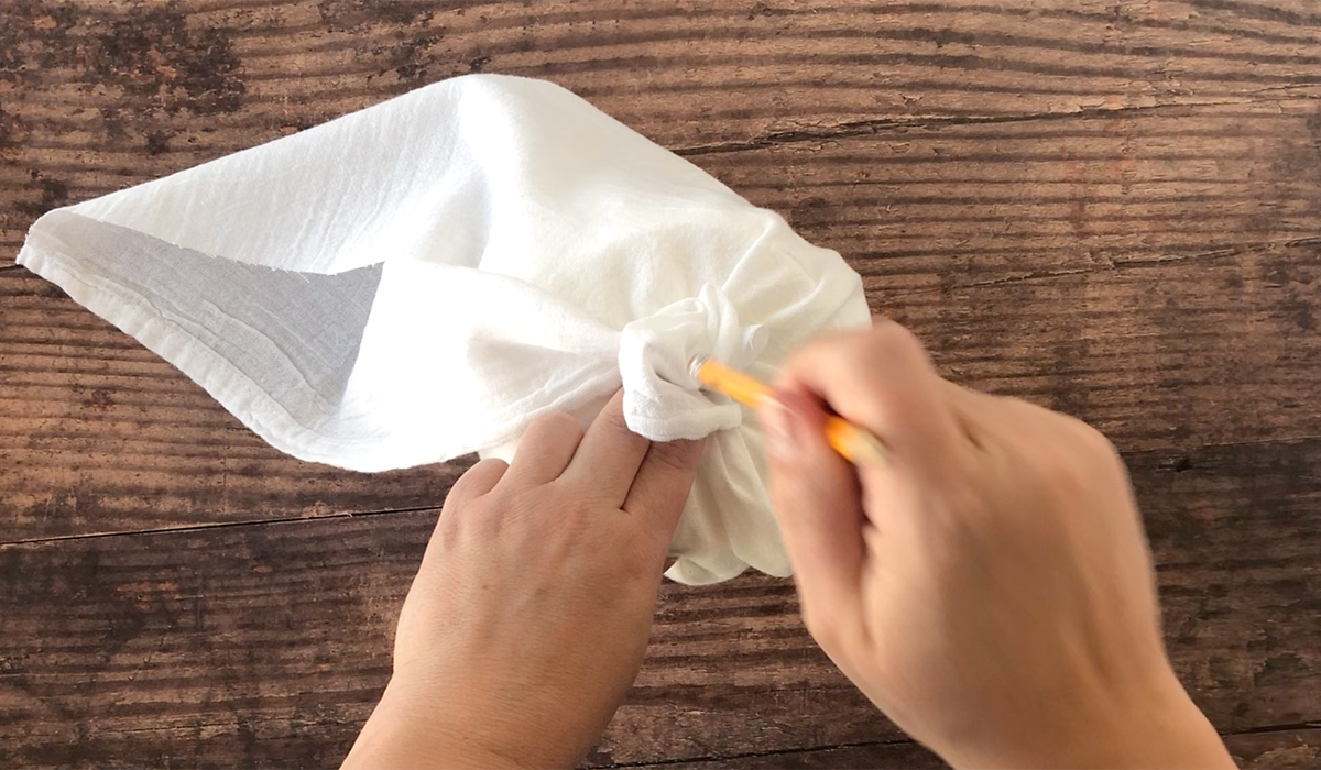 White fabric wrapped around roll of toilet paper; hands using a pencil to stuff excess fabric inside toilet paper roll