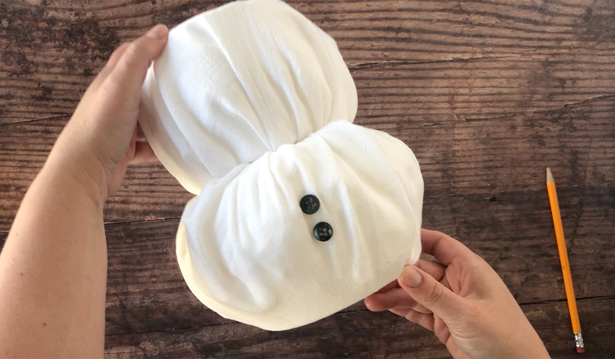Two rolls of toilet paper wrapped in white fabric stacked atop each other with two black buttons on the lower roll