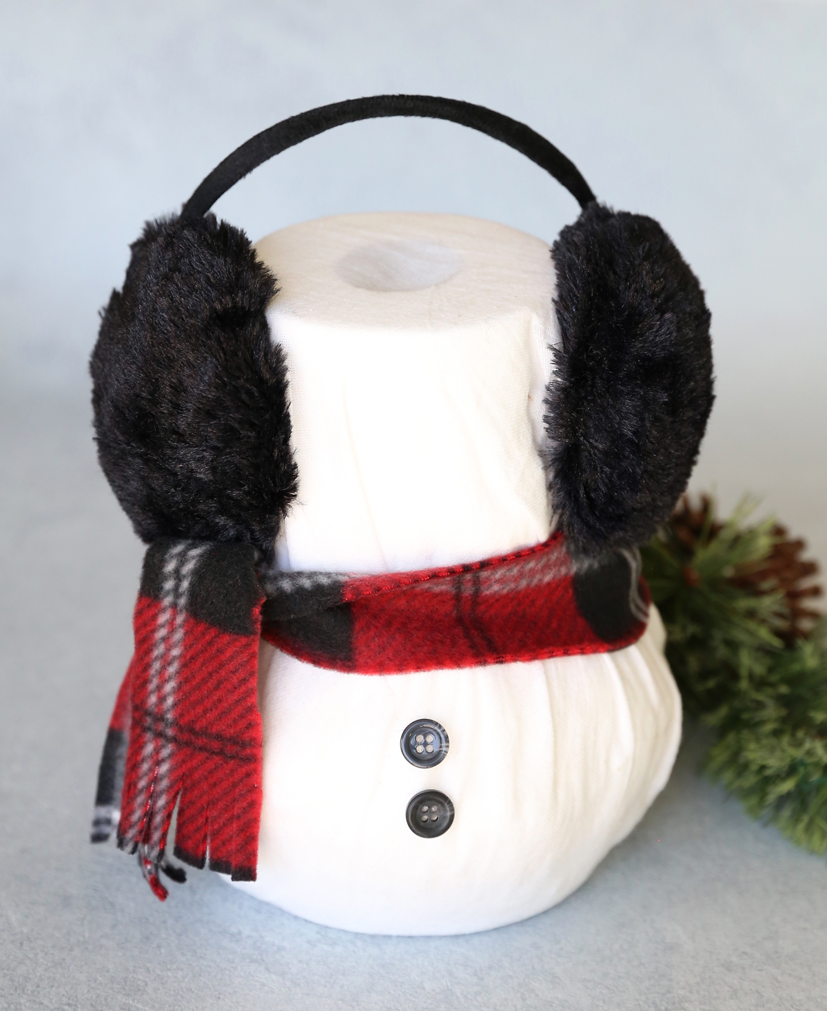Snowman made from two rolls of toilet paper with fleece scarf and earmuffs