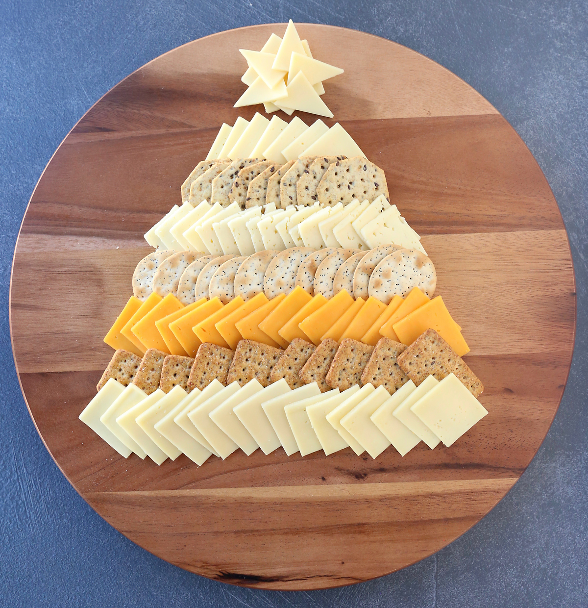 Cheese slices and crackers arranged in triangle Christmas tree shape