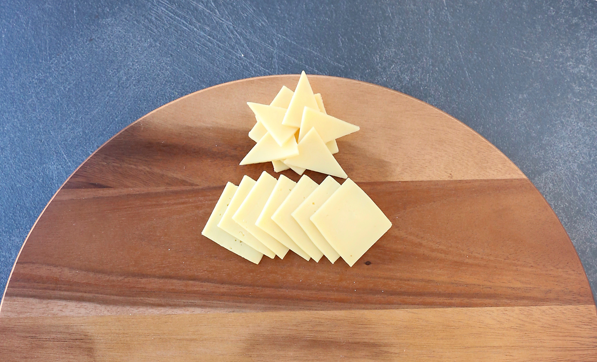 Cheese triangles arranged into star, with short row of white cheese slices layered beneath it