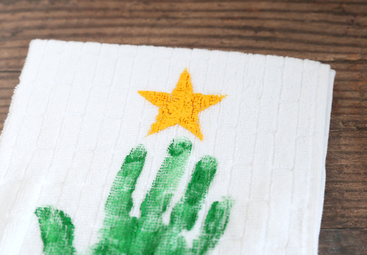 Towel with a green handprint and yellow star above it
