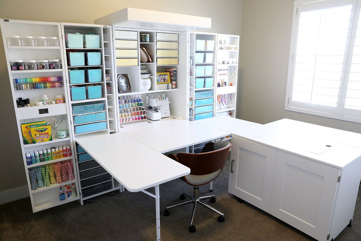 Wall sized craft storage system with multiple shelves and bins to hold supplies as well as a pull out table
