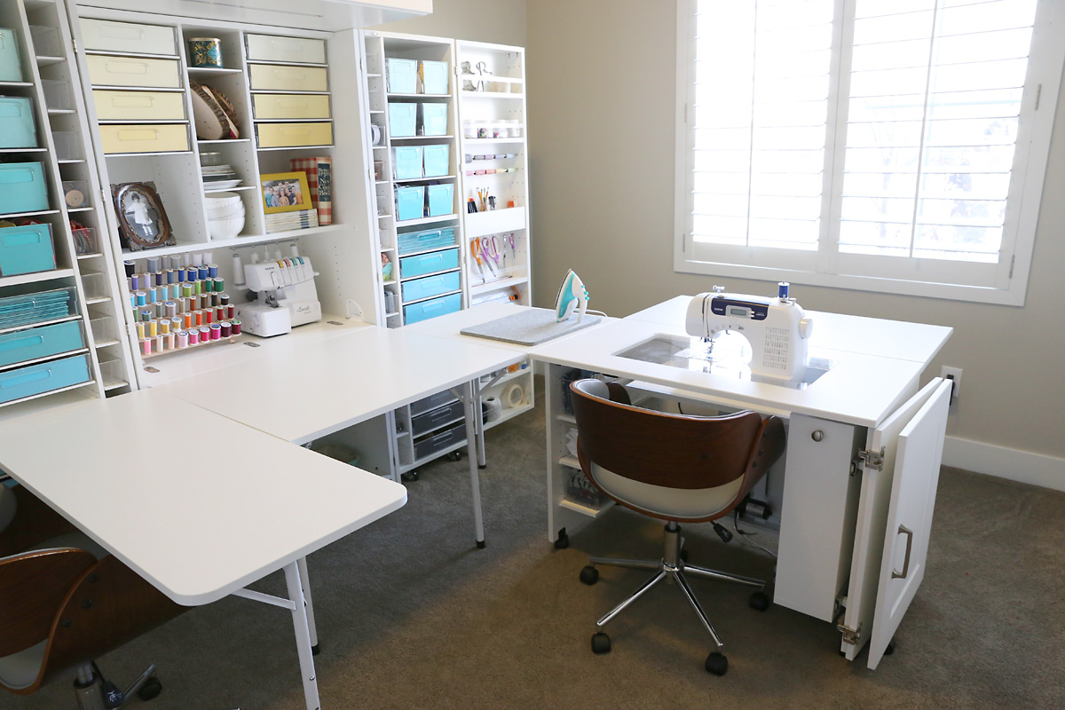 An office with a wraparound sewing desk and shelving for craft storage