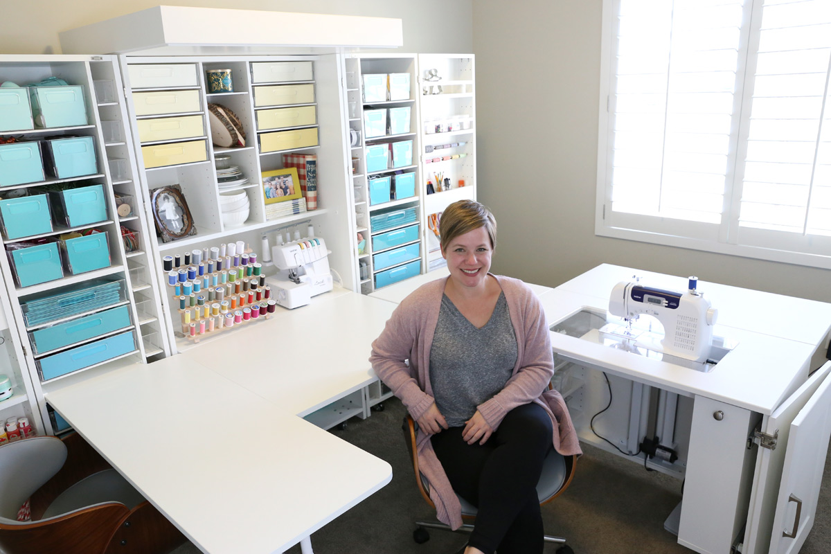 A person sitting at a desk in front of set of craft shelves, with a sewing machine and multiple bins in it