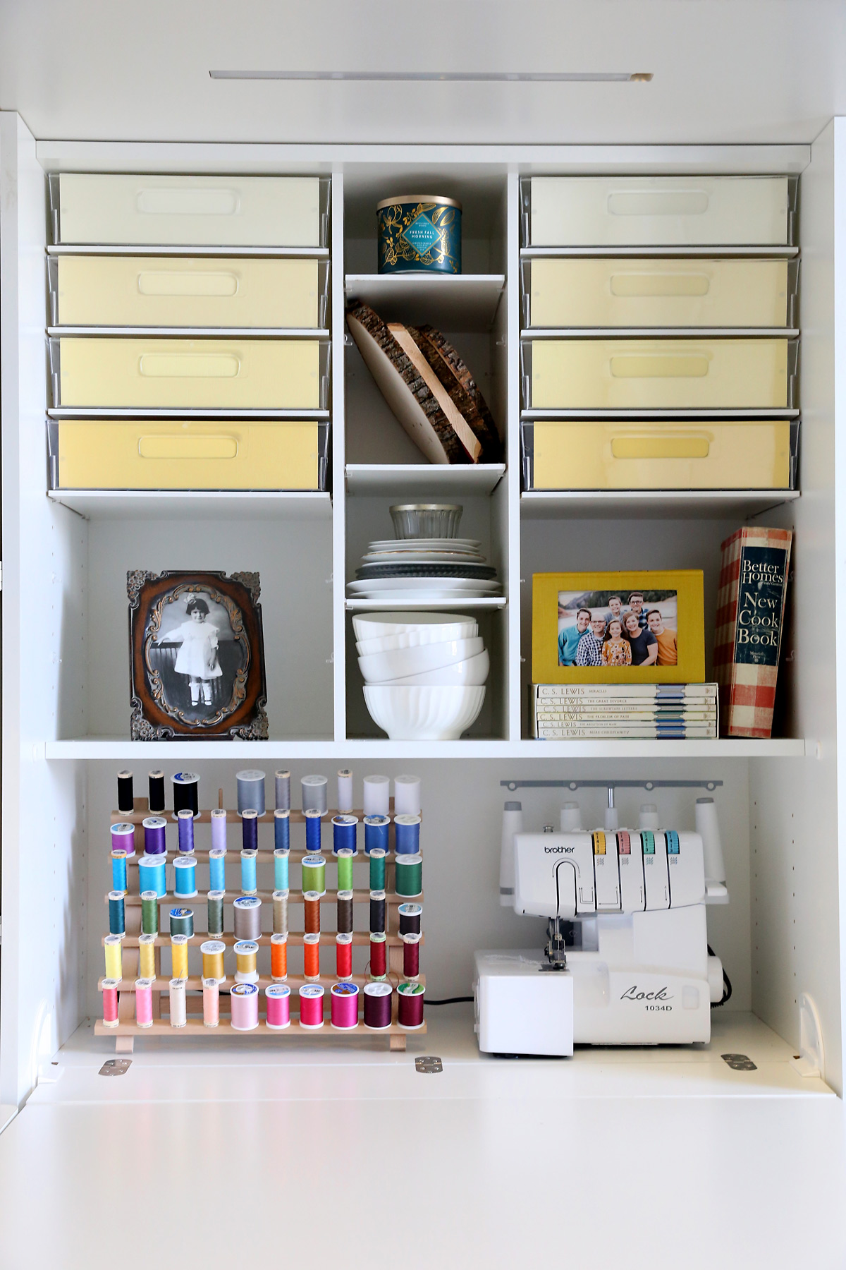 Shelves in a DreamBox with bins, books, sewing machine and thread spool