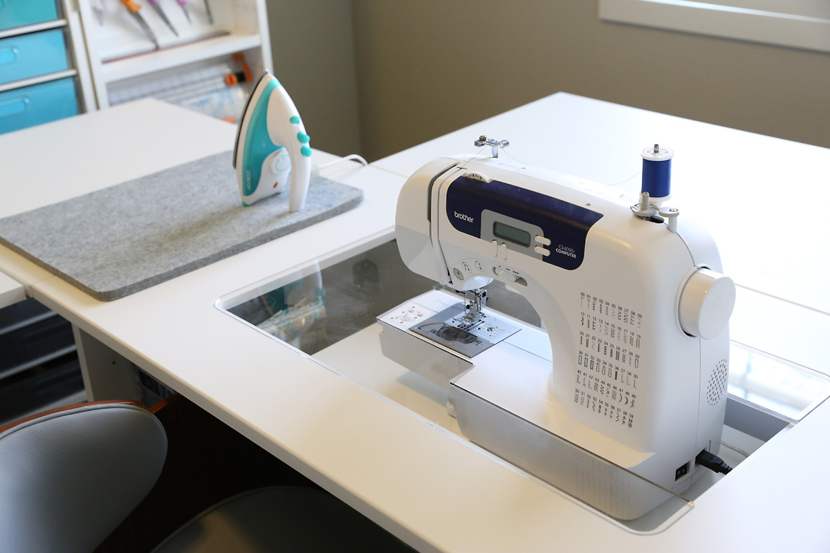 A sewing machine in a custom sewing desk called the Sew Station