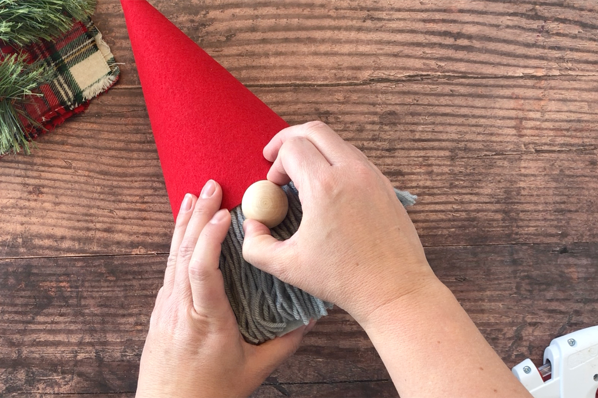 Hand holding wood bead that\'s been glued on for the gnome\'s nose
