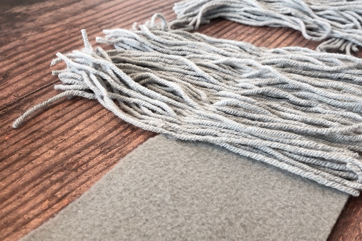 Grey yarn placed over strip of gray felt