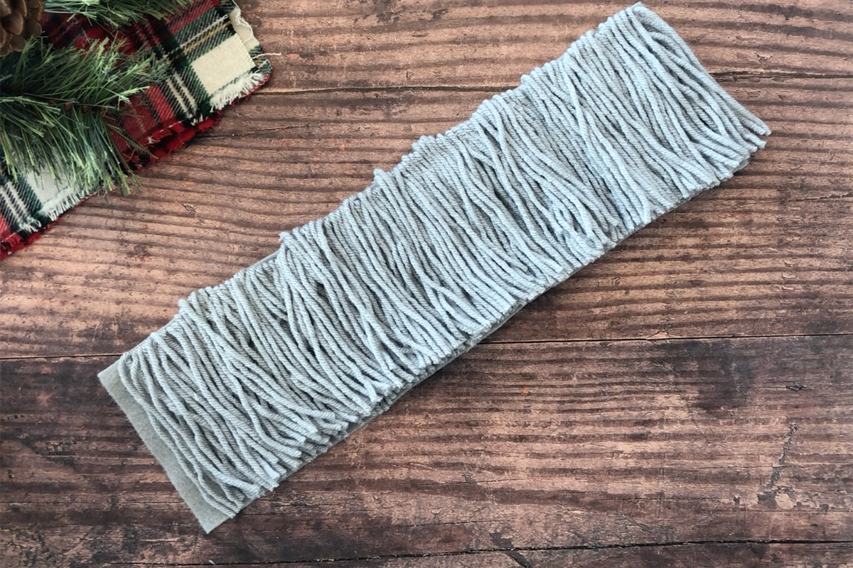 Strip of felt covered with grey yarn and trimmed neatly