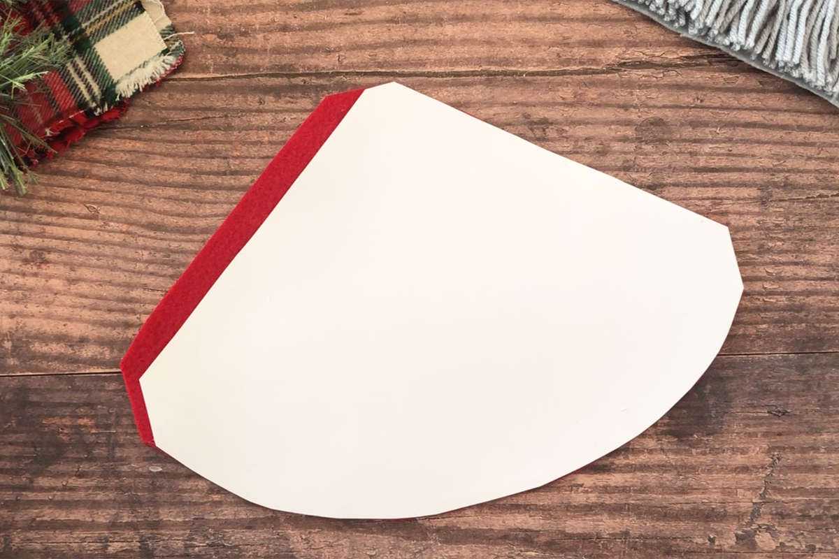 Triangle shape with rounded bottom edge placed over red felt to create gnome hat