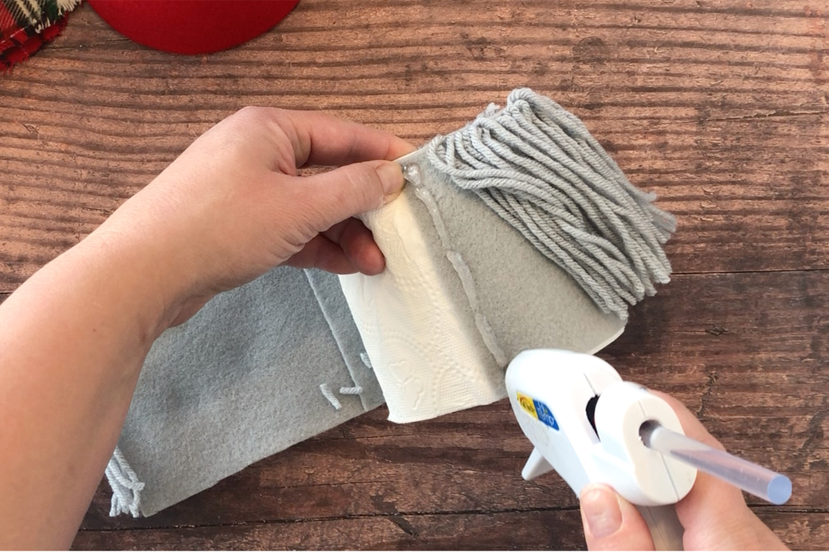 Hand hot gluing the yarn covered felt around a roll of toilet paper