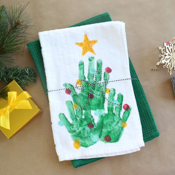Kitchen towel with Christmas tree made from handprints on it, tied with twine as a gift