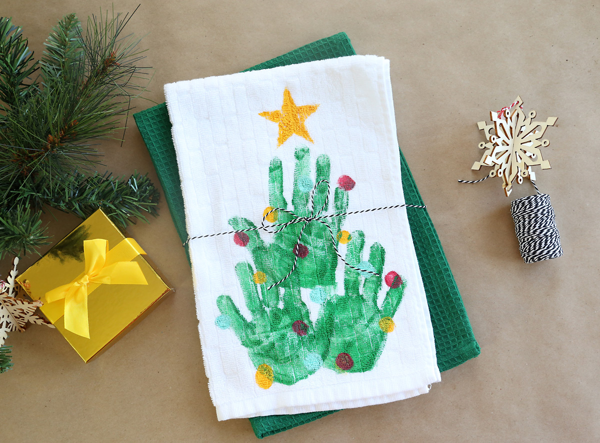 Kitchen towel with a handprint Christmas tree on it, tied with twine as a gift