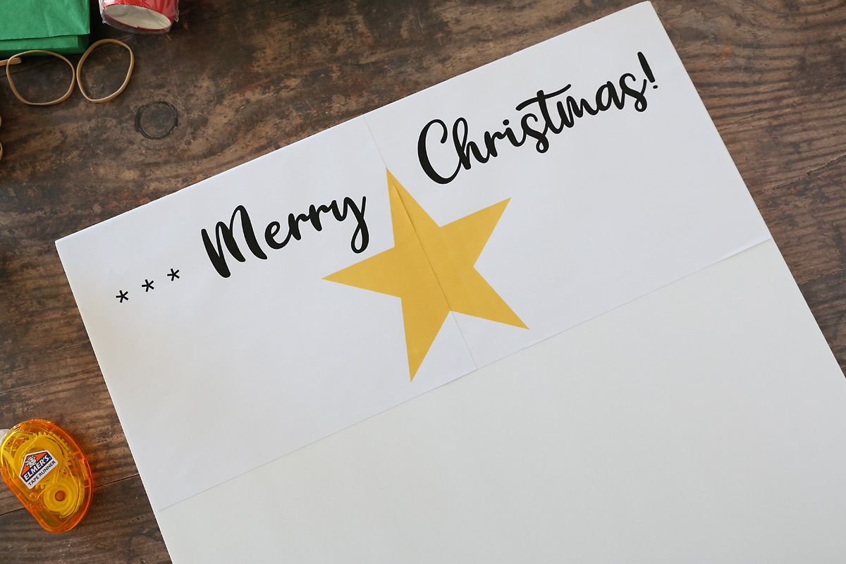 Large poster board that says Merry Christmas! and has a yellow star on top