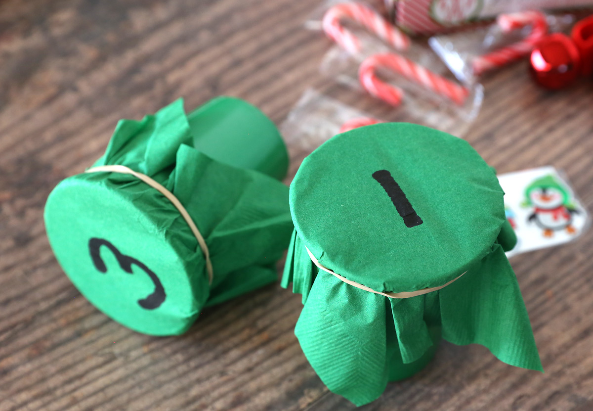 Cups with green napkins rubber banded around the top and numbers on them