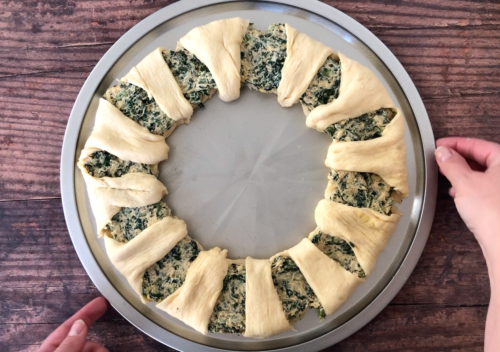 Raw crescent dough slices arranged in a wreath shape filled with spinach dip on a pizza pan