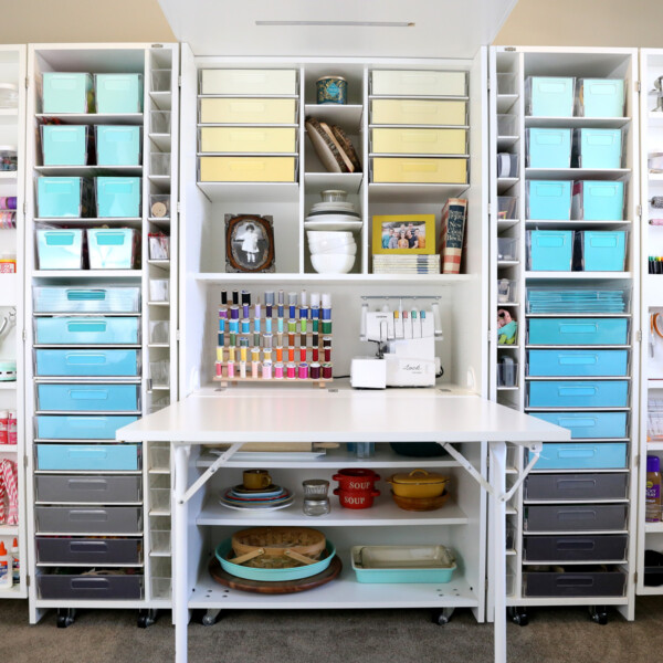 Wall sized craft storage system with multiple shelves and bins to hold supplies as well as a pull out table; full of color coordinated bins