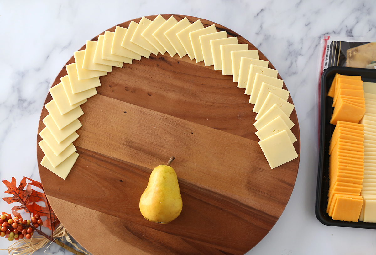 Circular cutting board with pear in bottom middle and white cheese slices fanned around the top two thirds of the edge