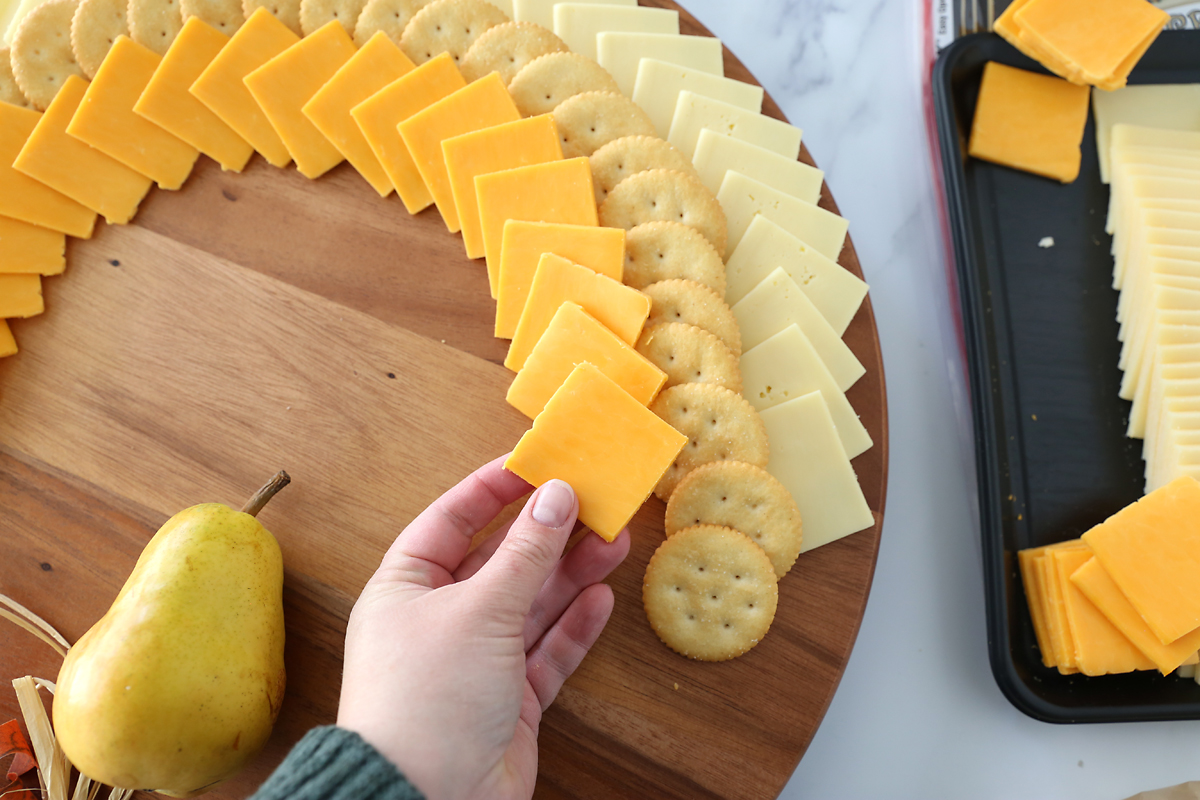 And adding rows of cheese slices and crackers, working in from the outside