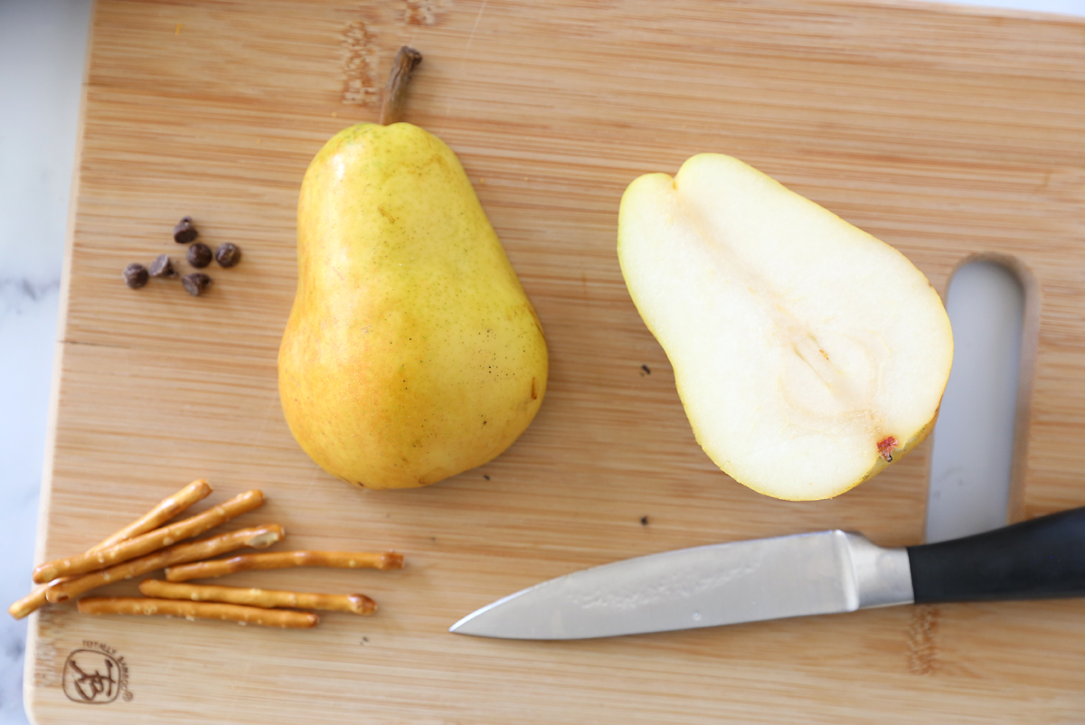 Pear sliced in half from top to bottom with mini chocolate chips and pretzel sticks