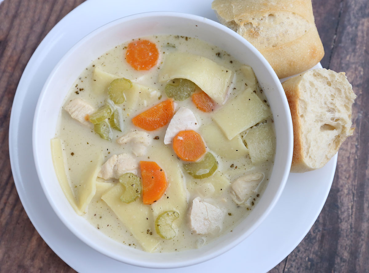 A bowl of creamy chicken noodle soup with carrots and celery and bread roll